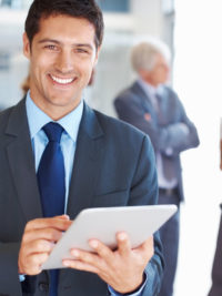 Portrait of smiling young business man working on digital tablet with executives in background